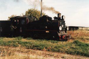 Parowóz Px48-1754 na tle pudła wagonu dwuosiowego.